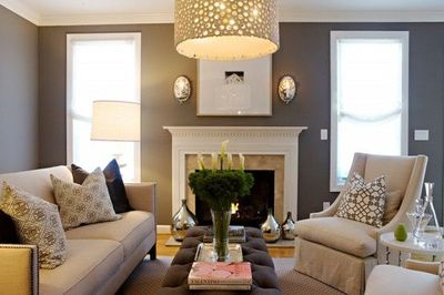 Chic gray living room design with gray purple walls paint color, hammered metal sconces, linen sofa with nailhead trim, white, slip-covered chairs with Windsor Smith Pelagos Insignia fabric pillows, gray & purple tufted rectangular ottoman, chandelier...