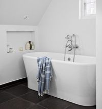 Freestanding bath, recessed storage.