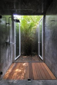 shower doors open out to enclosed patio. (Wood floor/drain might be a pain to keep clean and smelling fresh.)