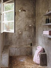 concrete shower, benches, shelves. Love the window, but it needs to open out, not in. Pebble floor!