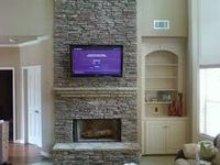 tv on brick fireplace, shelving to right side.