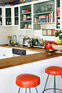 Red bar stools with white cupboards and timbre table tops. cute.