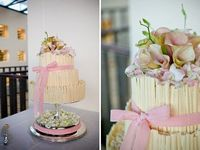 Soft pink and white chocolate wedding cake laden with pale pink lilies and tied with a light pink ribbon. Photo: Judy Stofberg