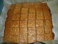 The making of easy toffee. A pan covered in soda crackers. Boil 1/2 c butter and 1/2 c brown sugar, 1t vanilla, for 3 min (no stirring) and pour over crackers. bake in oven 7 min. Take out and sprinkle choc chips over top, wait 2-3 min til soft an...