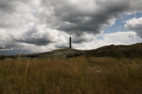 smoke stack rising over green pasture